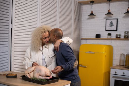Tender African American husband kissing positive black wife with closed eyes while standing near counter with uncooked turkey during cooking in modern kitchen