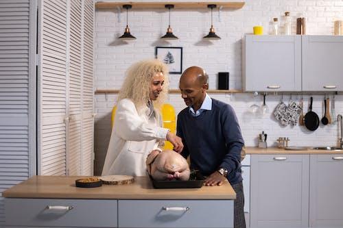 Black couple preparing turkey for dinner