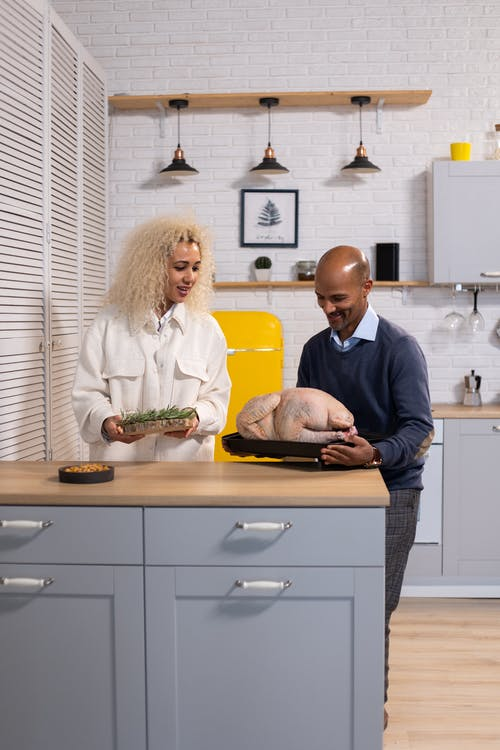 Cheerful black couple cooking turkey in kitchen