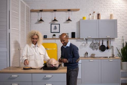 Positive black couple preparing turkey in kitchen