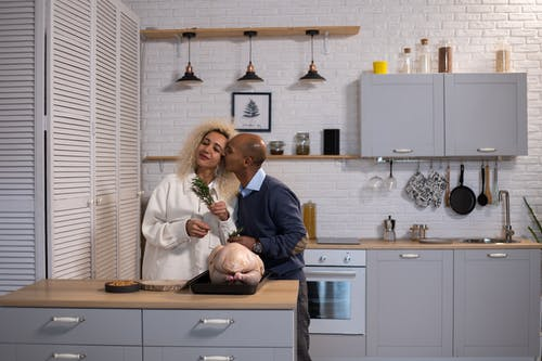 Loving black man kissing woman in kitchen with turkey