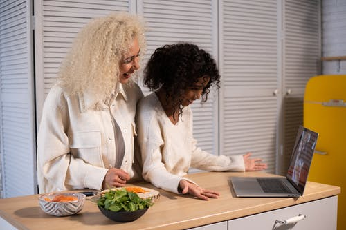 Side view of happy African American woman and girl having video call on modern laptop at wooden table with food in kitchen