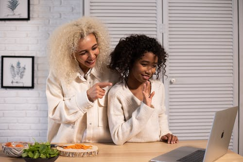 Cheerful black mother and daughter waving hands while having video call
