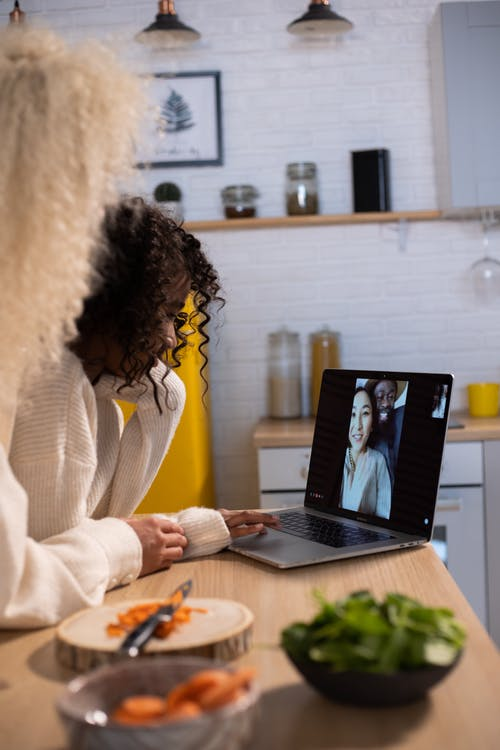 Crop mother and black daughter having video chat on laptop