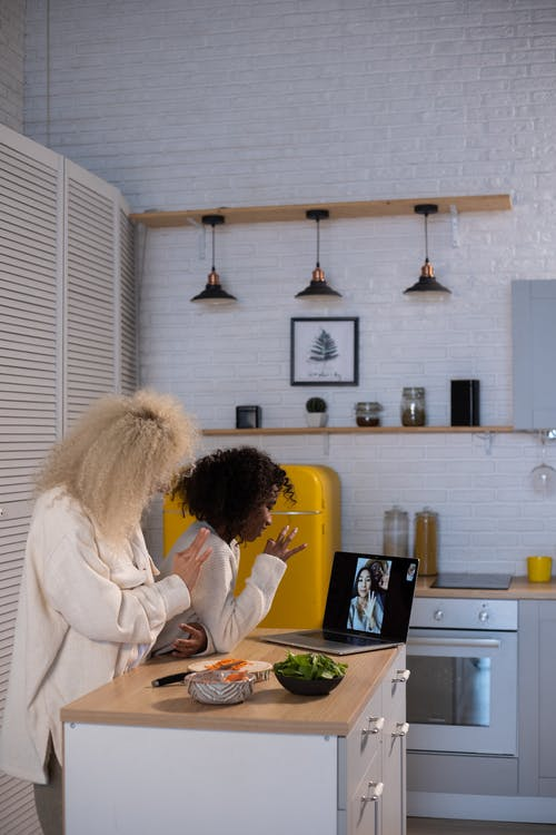 Side view of anonymous woman and African American girl waving hands while having video chat on laptop in kitchen at home