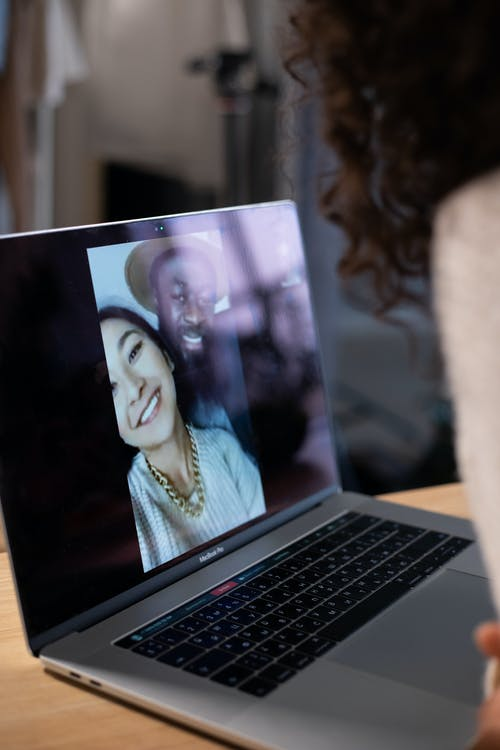 Crop woman making video call on laptop