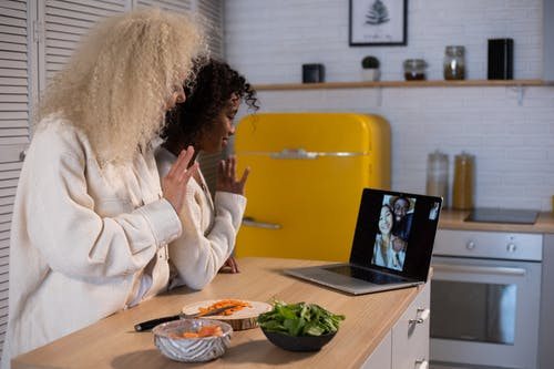 Side view of African American mother and girl waving hands while making video chat on laptop at kitchen counter with food