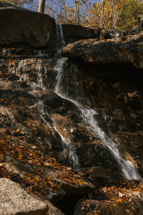 Rocky formation with rapid waterfall in forest