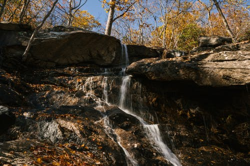Fast waterfall flowing through heavy rocks in autumn forest under bright clear blue sky