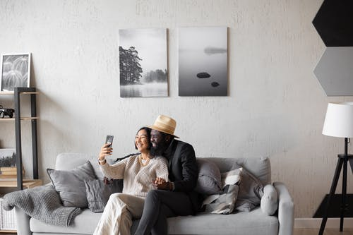 坐在灰色的沙發上的棕色外套的女人