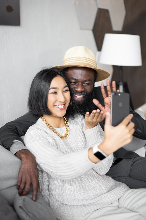 Positive diverse couple waving hands while video chatting on smartphone