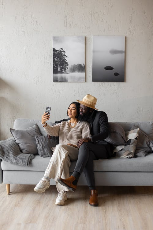 Full body of content Asian woman and African American man having video call while sitting on couch with crossed legs in room