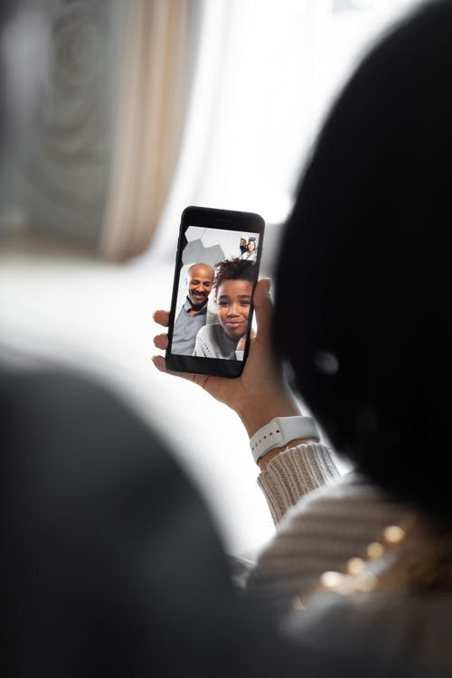 Back view of anonymous female having video chat with black man and girl in light room on blurred background at home
