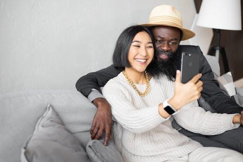 白色針織毛衫和米色帽子坐在灰色的沙發上的女人
