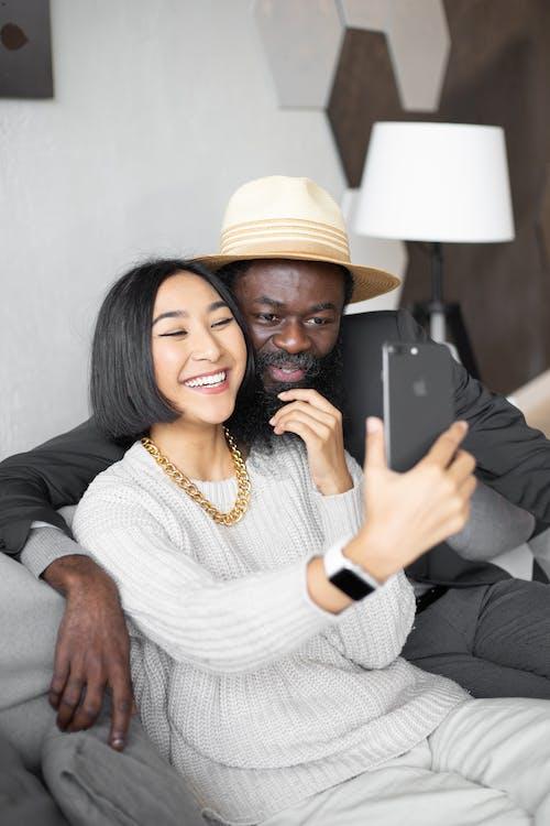 Femme En Pull En Tricot Blanc Tenant Un Smartphone Noir