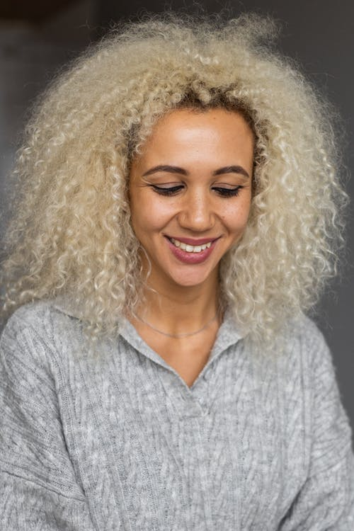 Cheerful African American female with curly blond hair wearing casual gray outfit smiling and looking down while standing in room