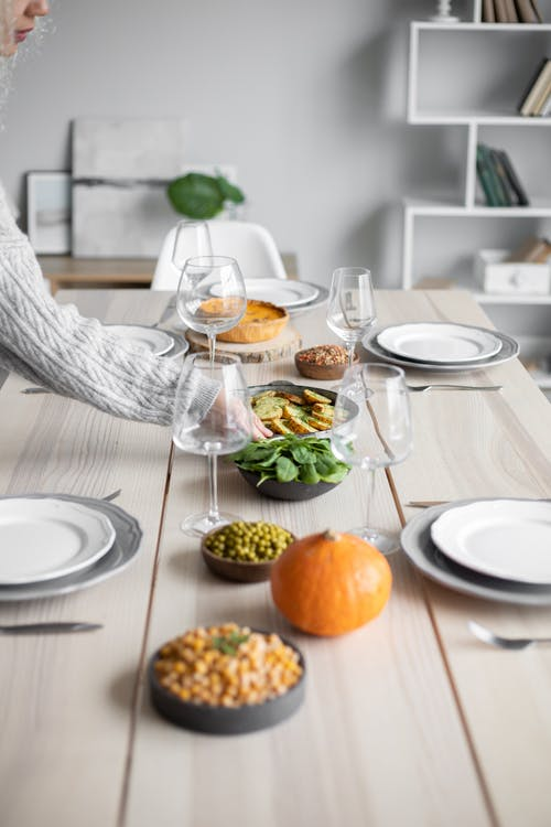 Crop person serving table with food