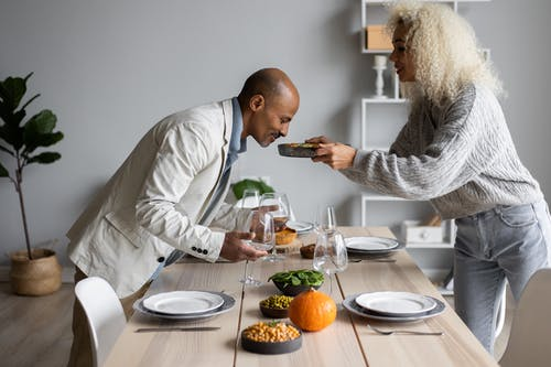 Side view of African American man smelling fresh meal while standing at served table with dishware and food with black wife
