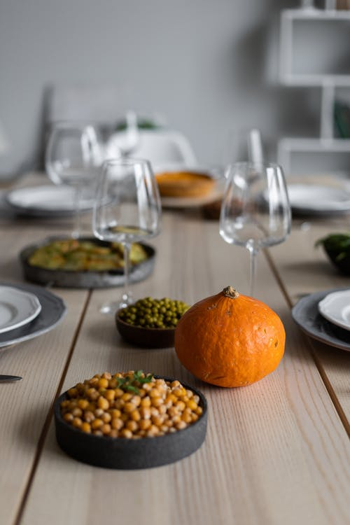 From above of fresh beans in bowls and ripe pumpkin placed on wooden table near empty plates and glasses for guests