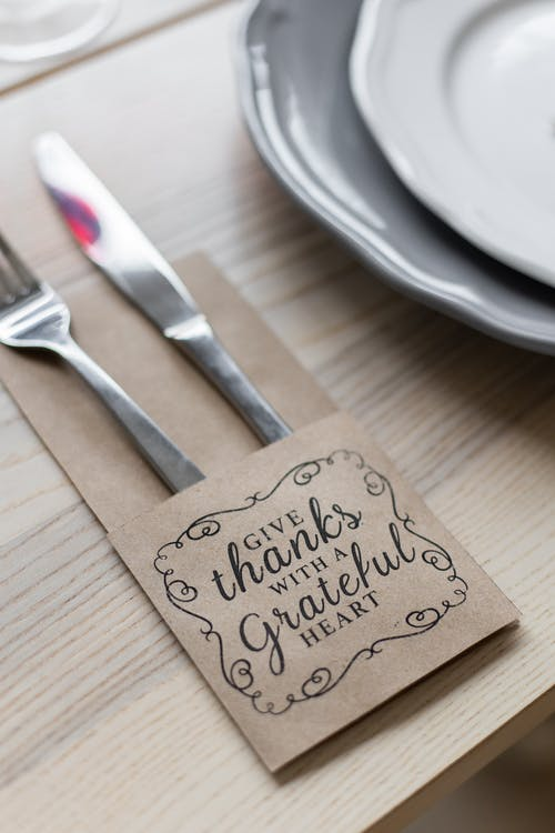 From above of metal shiny fork and knife placed in paper cover with inscription for Thanksgiving near plates on wooden table