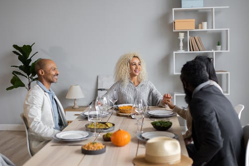 Happy multiracial people sitting at wooden table served with vegetarian food while having dinner together