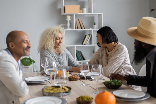 Cheerful multiracial people sitting at wooden table served with vegetarian food and talking to each other while having dinner together
