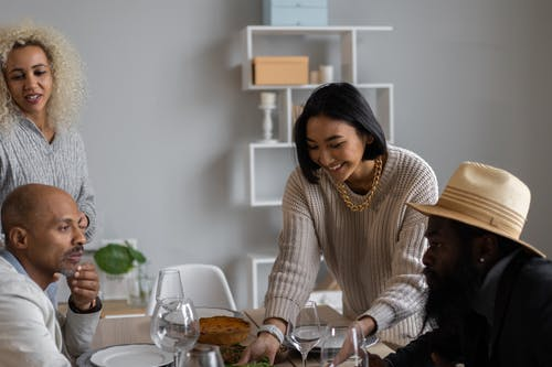 Positive diverse people in casual clothes sitting at table served with food while having dinner