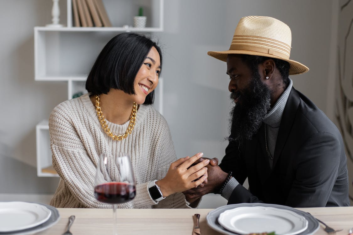 Loving multiracial couple looking at each other holding hands while sitting at table with plates and wine and having dinner