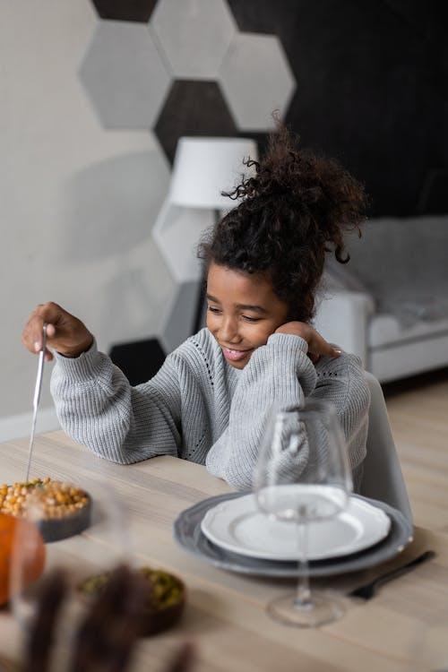 Smiling black girl sitting at table