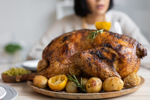 Palatable roasted turkey with potatoes and lemon on wooden round tray placed on table for celebrating Thanksgiving Day