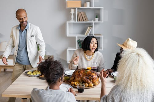 From above of glad diverse people speaking with each other while sitting at wooden table with food and having Thanksgiving dinner
