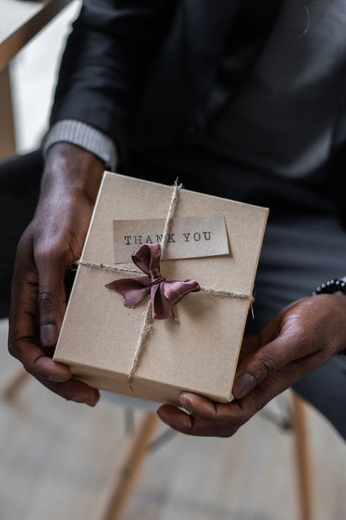 Crop black man with gift box