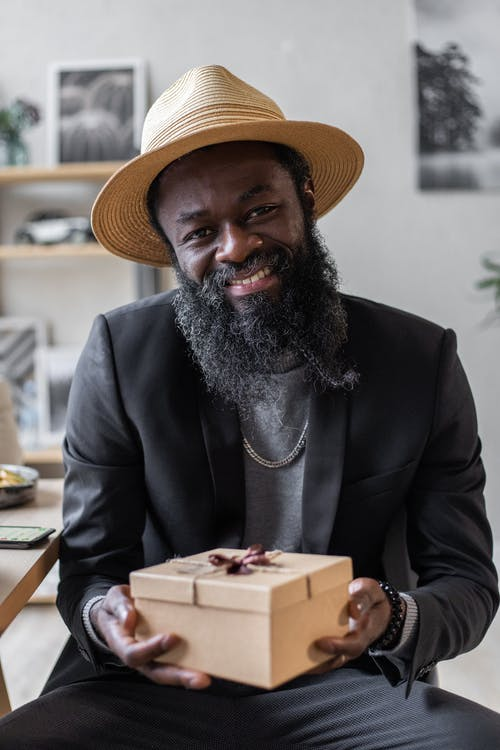 Cheerful adult African American male with beard in jacket and hat with carton gift box looking at camera