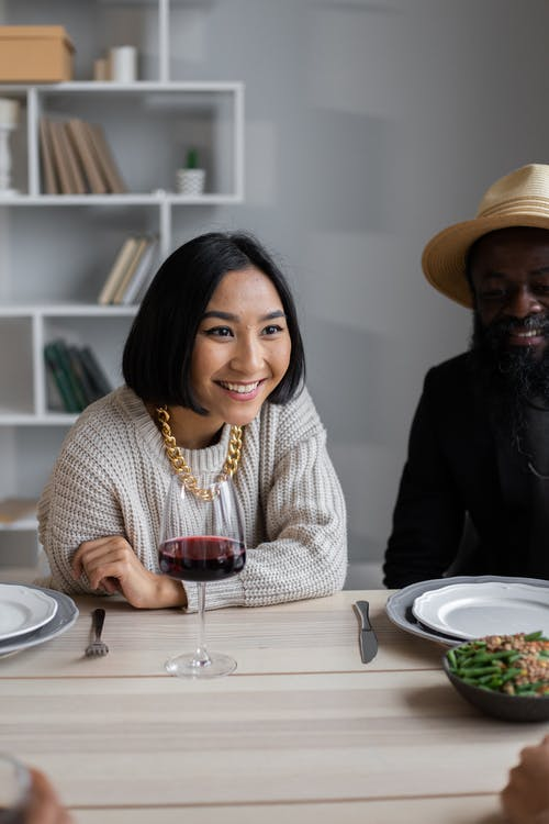 Cheerful diverse couple sitting at wooden table and speaking with guests while having dinner with guests