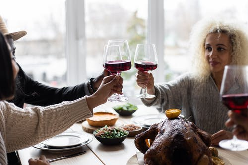 Multiethnic people clinking glasses having dinner