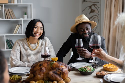 Positive multiethnic couple drinking wine with guests