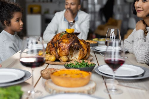 Crop multiethnic people sitting at wooden table served with wine and roasted turkey while having dinner on Thanksgiving