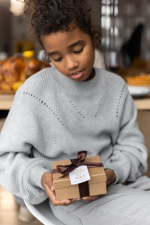 Calm black girl with gift box