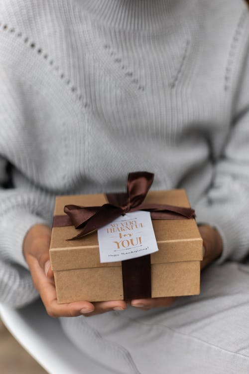 Crop unrecognizable female in knitted sweater with carton present box with bow and small postcard