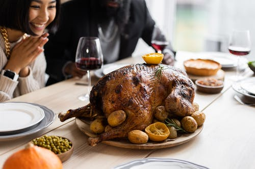 Cheerful multiethnic couple sitting at table with roasted turkey