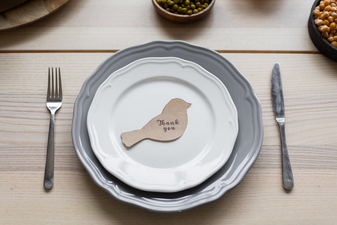 Top view of carton postcard cutout in shape of bird with printed Thank You inscription placed on plate on Thanksgiving dinner