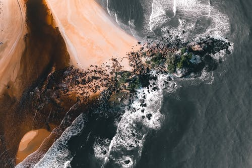 Drone view of rippled ocean with fast water flows on sandy shore with rocky formations