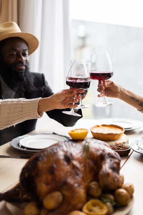Crop diverse friends clinking glasses having Thanksgiving dinner