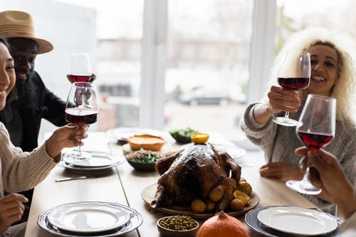 Glad diverse adult friends sitting at table with tasty dishes and toasting with glasses of wine during celebration of Thanksgiving Day