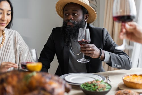 Positive diverse adult friends drinking wine while sitting at table served with delicious dishes and celebrating Thanksgiving Day