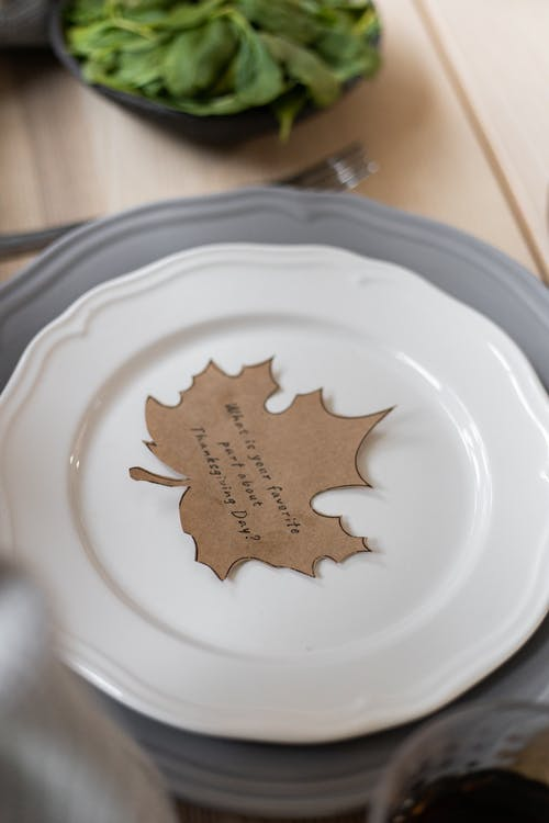 From above of cardboard postcard cutout in shape of maple leaf with inscription on Thanksgiving Day placed on porcelain plate on table for dinner