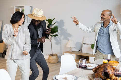 Happy multiethnic friends dancing together near table with dishes