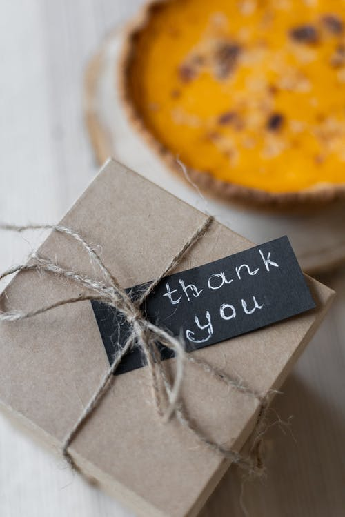 High angle of cardboard present box tied with rope and decorated with small postcard with Thank You inscription place on table near pie on Thanksgiving
