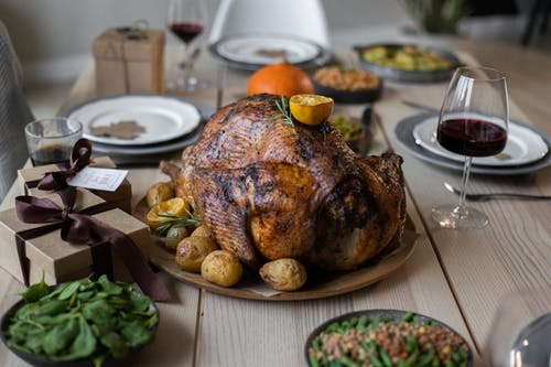 High angle of appetizing roasted turkey and glasses of wine with other dishes placed on wooden table prepared for celebrating Thanksgiving Day