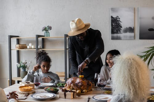 Cheerful diverse friends celebrating Thanksgiving Day with turkey